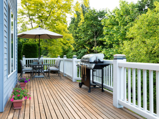 Cape Cod home with wooden deck, white railing, patio furniture, gas grill